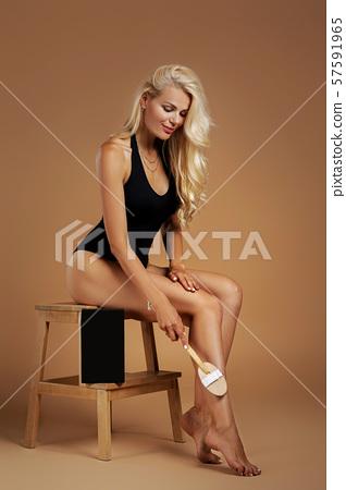 beautiful woman making a scrub massage with big brush. 57591965