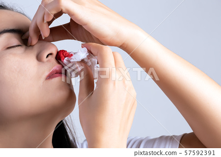 Nosebleed , a young woman with a bloody nose. 57592391
