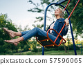 Carefree happy woman on swing outdoors 57596065