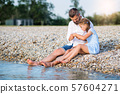 Side view of father and small daughter on a holiday sitting by the lake. 57604271