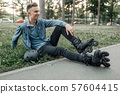 Roller skating, young skater sitting on the ground 57604415