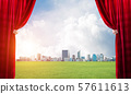 Green meadow behind red curtain and hand holding it 57611613