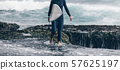 Woman surfer with surfboard going to surf 57625197
