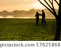 Silhouette of senior couple doing Tai Chi exercise in the park at sunrise. 57625868