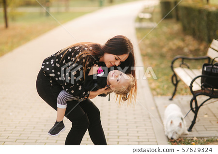 Mother and little daughter walking in autumn weather. Stylish little daughter and her beautiful 57629324
