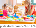 Group of children and teacher playing in kindergarten 57636376
