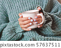 Female hands holding hot cup of coffee or tea. 57637511