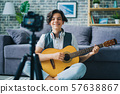 Portrait of teenage blogger recording video at home holding guitar smling 57638867