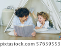 Loving mother reading book to cute child lying on floor in cosy tent indoors 57639553
