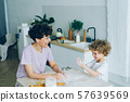 Mother and son having fun with flour cooking home-made cookies in kitchen 57639569