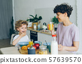 Young woman drinking orange juice while son eating cereal at table in kitchen 57639570