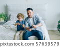 Cute kid playing video game with father holding joysticks having fun in bed 57639579