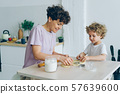Young family mother and son making home-made cookies at kitchen table 57639600