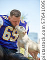 American football player with a dog posing on camera in a park. Copy space, sports banner. Concept 57641095