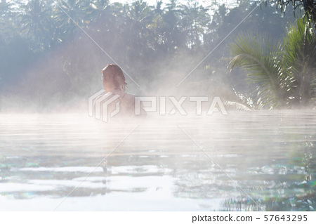A young woman relaxing in an infinity pool 57643295