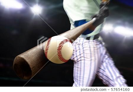 Baseball player hitting ball with bat in close up 57654160