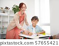 Smiling teacher helping schoolboy to write down letters 57655421