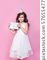 Cute little girl celebrate birthday. Child hold a box gift on pink background. 57655477