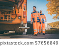 Two refuse collection workers loading garbage into waste truck 57656849