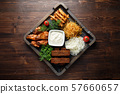 Hot appetizer on a wooden black plate on a dark wooden background. Restaurant menu 57660657
