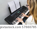 Young girl plays song on notes on synthesizer 57660785