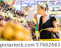 Woman buying fruits and vegetables at local organic food stoere. Market stall with variety of 57662663