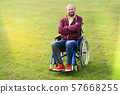 happy man on wheelchair surrounded by green grass 57668255