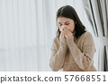Sick Asian woman using a tissue to sneeze at home 57668551
