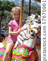 cute little girl riding on a carousel in an amusement park in the summer. 57670961