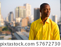 Young bald African businessman thinking against view of the city 57672730