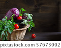 Bio purple eggplants in a basket on wooden 57673002