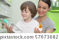 Beautiful woman and her son choosing between two products at drugstore 57673682