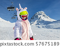 Cute adorable preschooler caucasian kid girl portrait with ski in helmet, goggles and unicorn fun 57675189