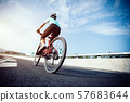 Woman cyclist  riding Mountain Bike on highway 57683644