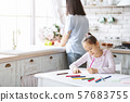 Cute girl drawing at kitchen table while her mother cooking 57683755