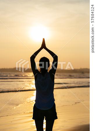Woman pracice yoga on sunset beach Rear View 57684124