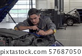 Auto mechanic looking under the hood of a car at the garage 57687050