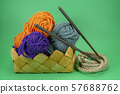 Knitting yarn balls, rope and needles in basket 57688762