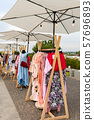 Racks with clothes outdoors. Designer sells 57696893