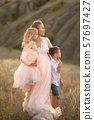 A young mother with children walks in a field at 57697427