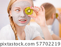 Happy young woman having face mask holding kiwi 57702219
