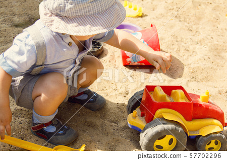 A little boy is plaing with red toy car in a sand 57702296