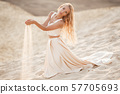 Portrait of beautiful bride is wearing fashion flying dress sitting on sand in the great desert in 57705693