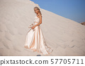 Beautiful bride is wearing fashion flying dress and wreath in the great desert in Dubai. 57705711