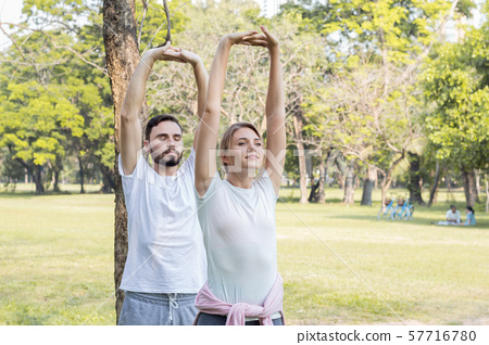 Young couples playing yoga in the park. Couples 57716780