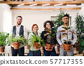 Group of young businesspeople standing in office, holding plants. 57717355