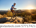 Sportsman cyclist balancing on back wheel on trial bicycle 57717421