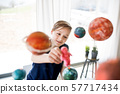 A small boy with model of solar system indoors. 57717434