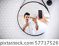 Young man with smartphone in the bathroom in the morning, taking selfie. 57717526