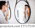 Young man shaving in the bathroom in the morning, daily routine. 57717549